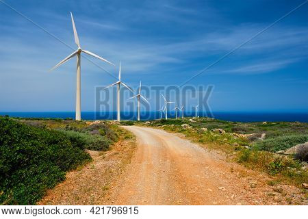 Green renewable alternative energy concept - wind generator turbines generating electricity. Wind farm on Crete island, Greece with road