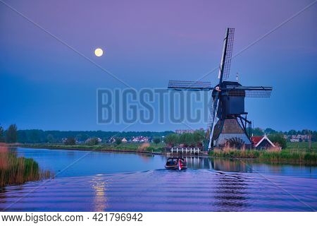 Netherlands rural lanscape with windmills at famous tourist site Kinderdijk in Holland in twilight with full moon and boat in canal