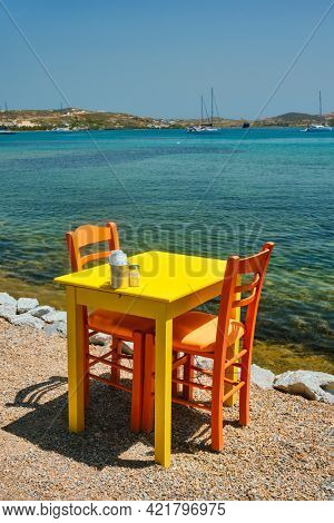 Yellow cafe restaurant table of street cafe with chairs on beach in Adamantas town on Milos island with Aegean sea with boats and yachts in background. Milos island, Greece