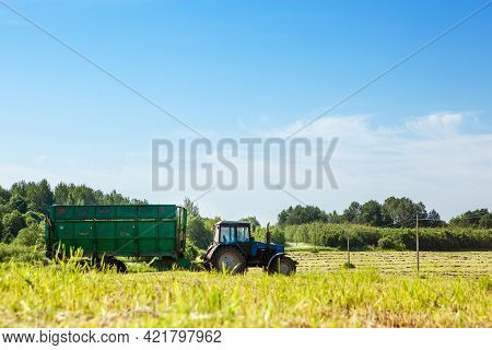 Tractor With A Trailer In The Field For Agricultural Work. Hay Making, Grassland. General Plan, Pano