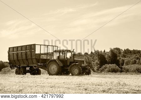 Tractor With A Trailer In The Field For Agricultural Work. Hay Making, Grassland. Copy Space. Monoch