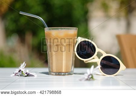 Ice Coffee Cyprus Frappe Fredo Side View On White Table, With Sunglasses. Summer Minimalistic Backgr