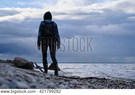 Woman Tourist With A Backpack Walks Along The Riverbank. Rainy Sky. Late Evening. Travel Outside The