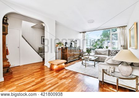 White Room With Parquet Wooden Floor Furnished With Vintage Wooden Cabinet And Gray Couch
