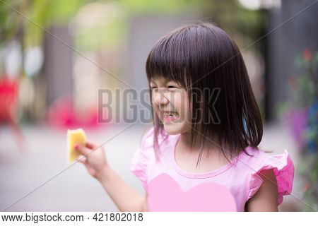 Portrait Of Asian Cute Girl Smile And Laughing During Eating Fruit. Kid Holding Ripe Mango. Happy Ch