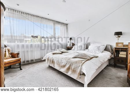 Simple Interior Of Modern Bedroom With Queen Size Bed With Cushions And Plaid Near Window And Armcha