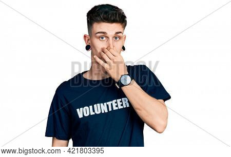 Young caucasian boy with ears dilation wearing volunteer t shirt smelling something stinky and disgusting, intolerable smell, holding breath with fingers on nose. bad smell