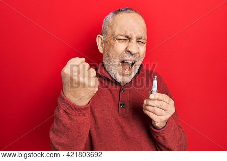Handsome mature man holding spark plug annoyed and frustrated shouting with anger, yelling crazy with anger and hand raised