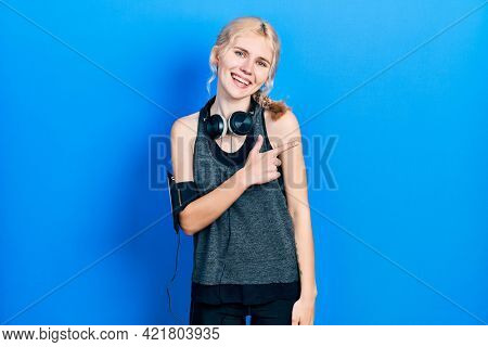 Beautiful caucasian woman with blond hair wearing sportswear cheerful with a smile of face pointing with hand and finger up to the side with happy and natural expression on face