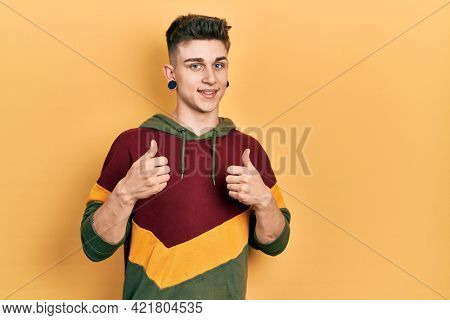 Young caucasian boy with ears dilation wearing casual sweatshirt success sign doing positive gesture with hand, thumbs up smiling and happy. cheerful expression and winner gesture.
