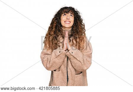 Young hispanic girl wearing winter clothes begging and praying with hands together with hope expression on face very emotional and worried. begging.