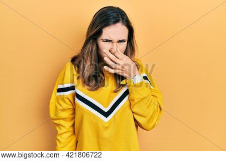 Young hispanic girl wearing casual clothes smelling something stinky and disgusting, intolerable smell, holding breath with fingers on nose. bad smell