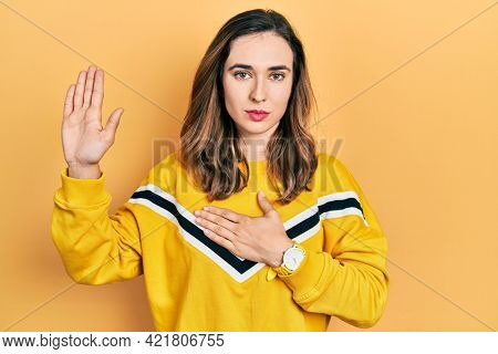 Young hispanic girl wearing casual clothes swearing with hand on chest and open palm, making a loyalty promise oath