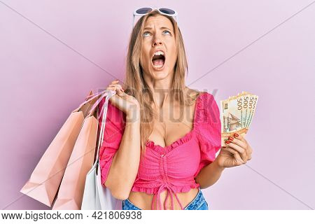 Beautiful caucasian woman holding shopping bags and 500 norwegian krone angry and mad screaming frustrated and furious, shouting with anger looking up.