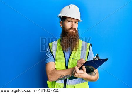 Redhead man with long beard wearing safety helmet holding clipboard skeptic and nervous, frowning upset because of problem. negative person.