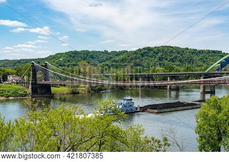 Wheeling, Wv - May 18, 2021: Old Suspension Bridge Carrying The National Road Above Coal Barge On Th