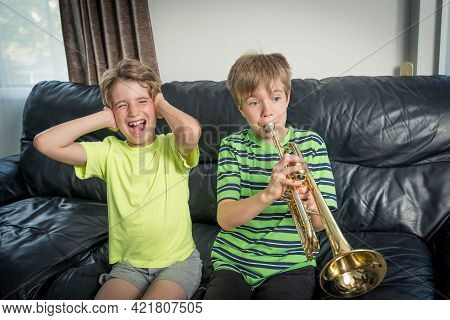 Two Kids Sitting On A Sofa.\\none Is Playing A Trumpet And The Other Child Annoyed Is Covering His E
