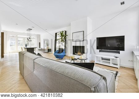 Spacious Luxury House Living Room With Sofa And Blue Armchair Against Workspace Corner With Bookshel