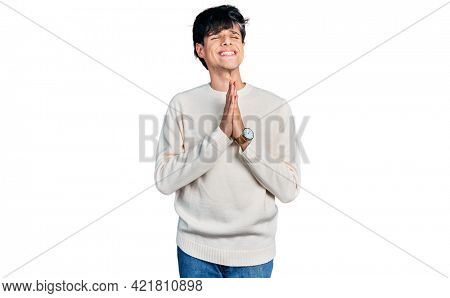 Handsome hipster young man wearing casual winter sweater begging and praying with hands together with hope expression on face very emotional and worried. begging.