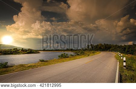 Empty Asphalt Road With Sunset. Scenic View Of Country Road Background. Street View Along A River.