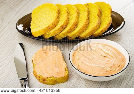 Slices Of Cornbread In Brown Dish, Table Knife, Sandwich, White Glass Bowl With Creamy Fish Oil On W