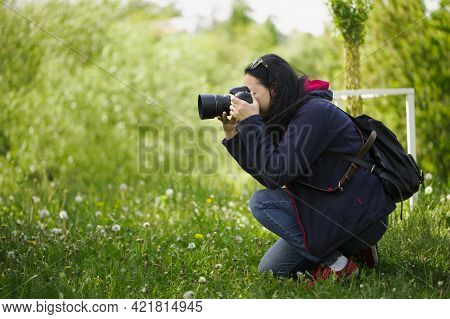 Girl Photographer With A Camera. Woman Tourist, Blogger, Photographing Nature. Spring Background. Co