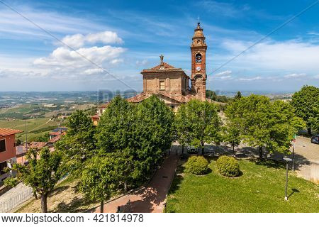 View of old catholic church among green trees under beautiful blue sky with white clouds in small town of Diano d'Alba, Piedmont, Northern Italy.