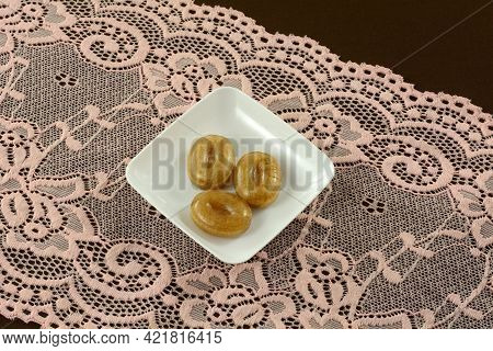 Thai Tamarind Hard Candy Pieces On Small Candy Plate On Pink Lace On Brown Tablecloth