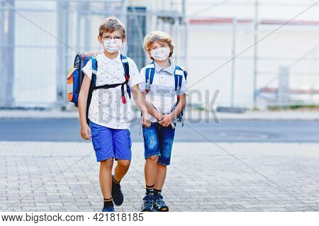 Two Kids Boys Wearing Medical Mask On The Way To School. Children With Satchels. Schoolkids On Warm