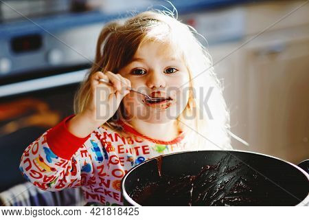 Cute Toddler Girl Eating Chocolate Dough Rests With Spoon And Fingers From Pot. Happy Child Licking