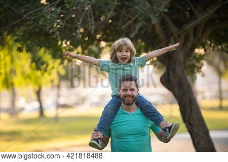 Portrait Of A Young Dad And His Child In The Park. Happy Kid Son Stretching Out Hands While His Fath