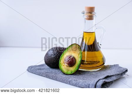 Pitcher Of Natural Oil And Fresh Ripe Hass Avocados. Preparing Food In The Kitchen. Ingredients. Con