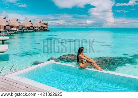 Luxury resort travel vacation destination idyllic overater bungalow villa woman relaxing by infinity pool. Social media influencer traveler luxurious high end lifestyle.