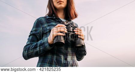 Young Unrecognizable Woman Explorer With Binoculars In Her Hands In The Background Sky.