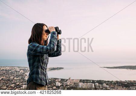 Woman Explorer Looks Through Binoculars In The Mountains.
