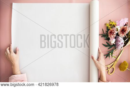 Woman unroll a paper on a pink table by a bouquet of flowers