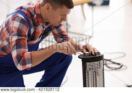Professional Technician Repairing Electric Halogen Heater With Screwdriver Indoors