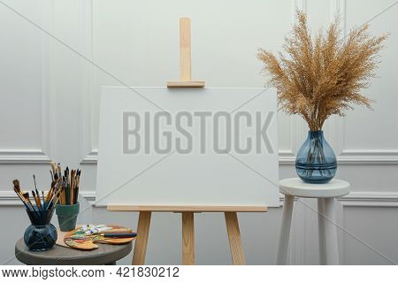 Easel With Blank Canvas, Brushes, Paints And Palette In Studio