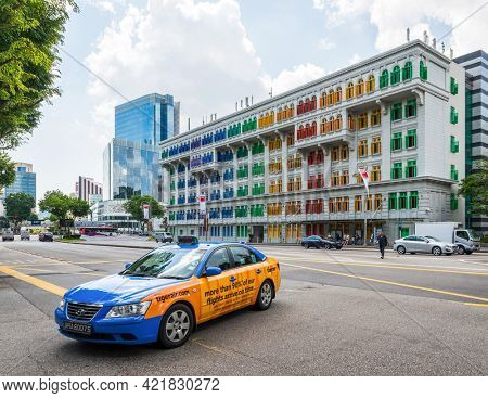 SINGAPORE - CIRCA JANUARY 2016: Blue and orange Hyundai taxi with the Old Hill Street Police Station in the background.