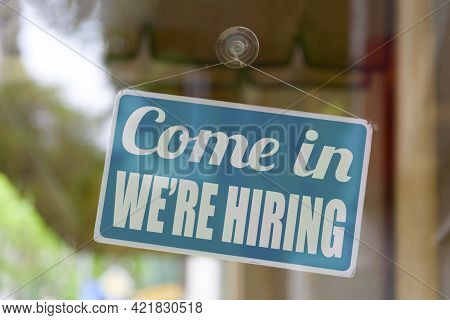 Close-up On A Blue Sign In The Window Of A Shop Displaying The Message: Come In We're Hiring.