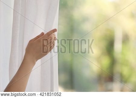 Woman Opening White Window Curtains In Room, Closeup. Space For Text