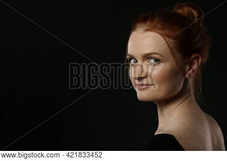Candid Portrait Of Happy Red Haired Woman With Charming Smile On Dark Background, Space For Text