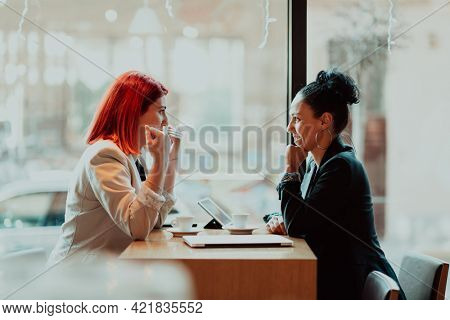 Two young business women sitting at table in cafe.Girl using laptop, smartphone, blogging. Teamwork, business meeting. Freelancers working...
