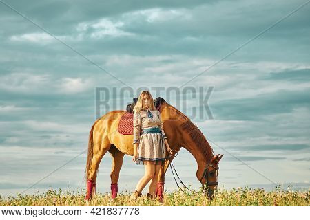 Girl With Horse In A Field In The Sunbeams Of The Sunset. Beautiful Sky Above The Horizon