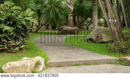 Walkway In Garden Of Public Park Among Greenery Trees, Flower Shrub And Bush, Grey Stone Pavement Wa