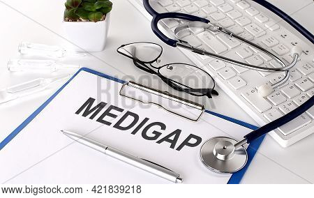 Medigap Text On White Paper On The White Background. Stethoscope ,glasses And Keyboard