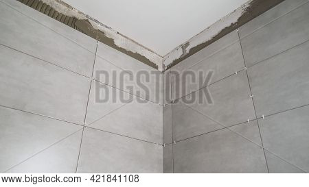 Tiled Walls. The Tiles Are Glued To The Wall. The Bathroom Wall Is Tiled With Gray Ceramic Tiles.