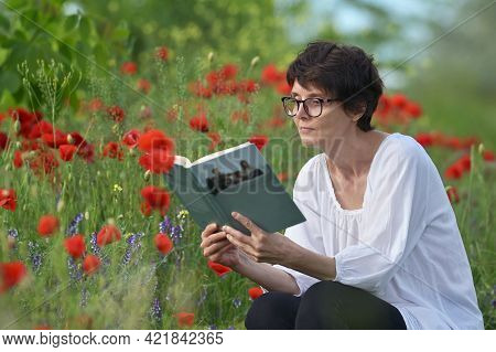 Woman In A Poppy Field Reading And Holding A Book