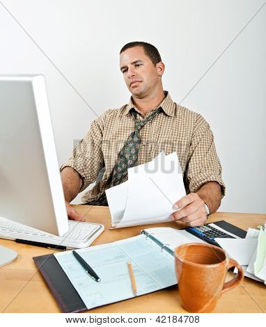 Tired Young Man At Desk Paying Bills