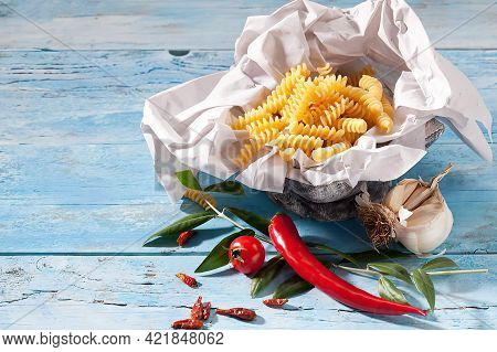 Uncooked Fusilli, Chili Pods, Garlic, Chili Pepper And Olive Twig
